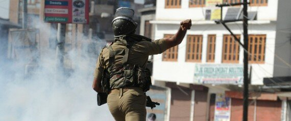 An Indian security personnel throws a rock towards Kashmiri protestors during clashes in Srinagar on April 17, 2015. Police arrested a prominent separatist leader in Indian-administered Kashmir on April 17, 2015 after he led a rally where supporters waved Pakistani flags and chanted pro-Pakistan slogans. Kashmir has been rocked by violent protests after the brother of a top rebel leader was killed by the army near the town of Tral in the south of the Kashmir valley.